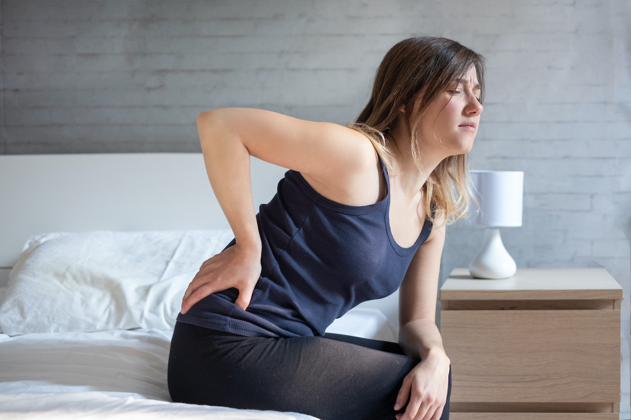 Woman waking up in the morning suffering backache